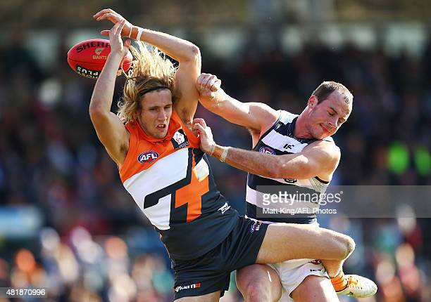 Nick Haynes of the Giants is challenged by Josh Walker of the Cats during the round 17 AFL match between the Greater Western Sydney Giants and the...