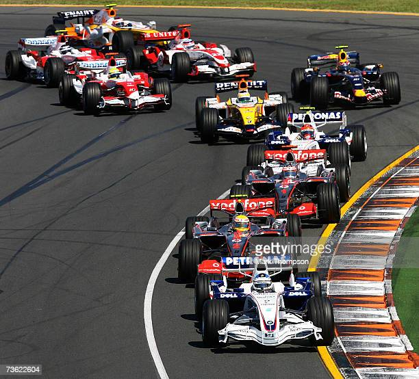 Nick Heidfeld of Germany and BMW-Sauber in second place on the opening lap races in front of Lewis Hamilton of Great Britain and McLaren Mercedes,...
