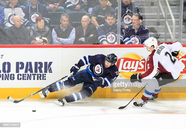 Nick Holden of the Colorado Avalanche looks on as Andrew Copp of the Winnipeg Jets falls to the ice while playing the puck during secondperiod action...