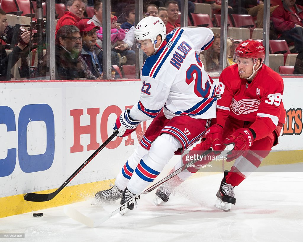 Nick Holden #22 of the New York Rangers battles along the boards for the puck with Anthony Mantha #39 of the Detroit Red Wings during an NHL game at Joe Louis Arena on January 22, 2017 in Detroit, Michigan.
