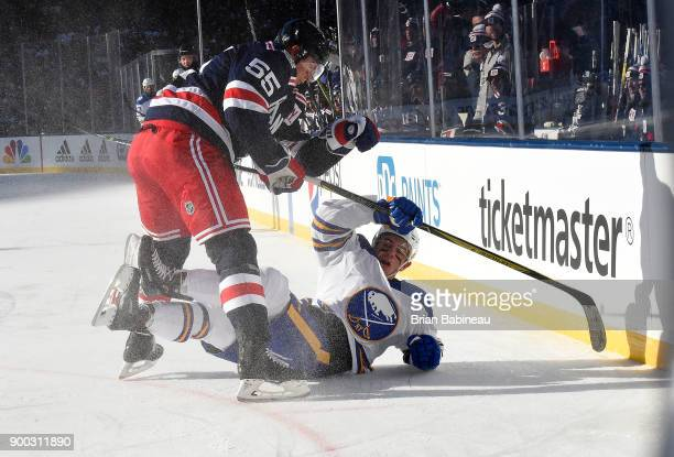 Nick Holden of the New York Rangers checks Evan Rodrigues of the Buffalo Sabres to the ice during the first period of the 2018 Bridgestone NHL Winter...