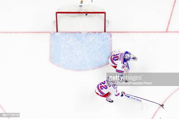 Nick Holden of the New York Rangers corals the puck as teammate Henrik Lundqvist guards his net after losing his stick against the Ottawa Senators in...