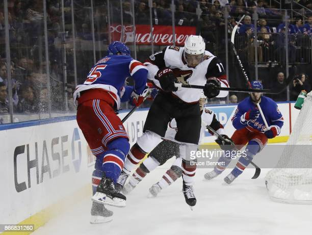 Nick Holden of the New York Rangers is hit by Brendan Perlini of the Arizona Coyotes during the first period at Madison Square Garden on October 26...
