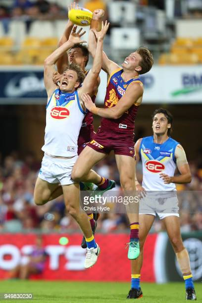 Nick Holman of the Suns and Alex Witherden of the Lions comepete for the ball during the round five AFL match between the Brisbane Lions and the Gold...