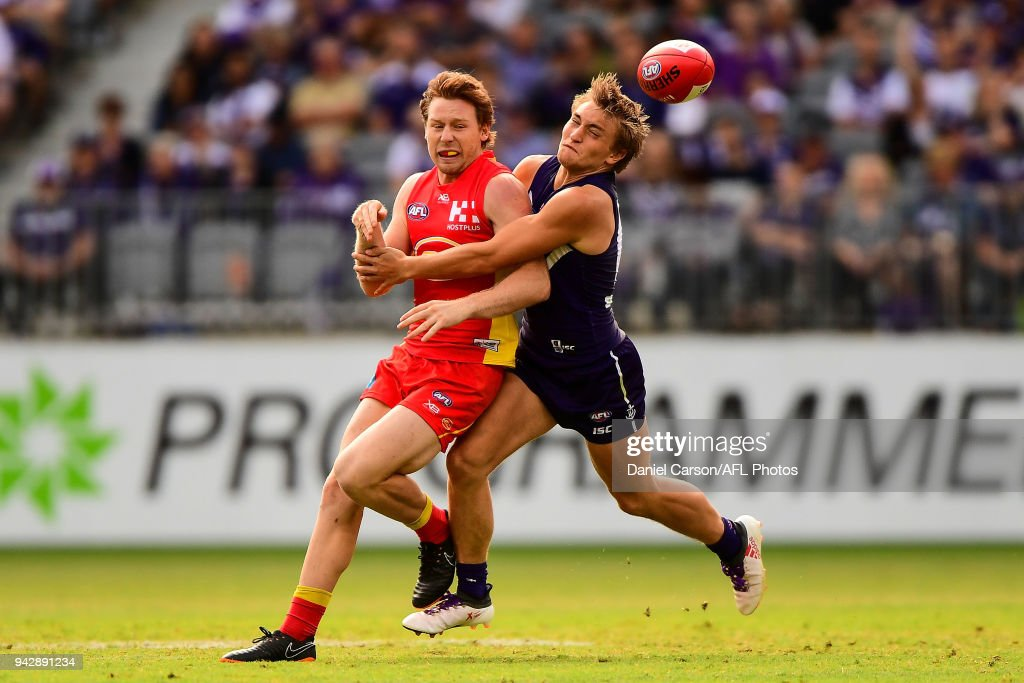 Nick Holman of the Suns is tackled by Mitchell Crowden of the Dockers during the 2018 AFL round 03 match between the Gold Coast Suns and the Fremantle Dockers at Optus Stadium on April 7, 2018 in Perth, Australia.