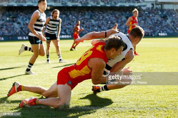 Nick Holman of the Suns tackles Mitch Duncan of the Cats during the round 10 AFL match between the Geelong Cats and the Gold Coast Suns at GMHBA...