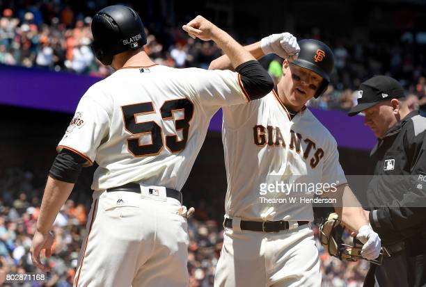 Nick Hundley and Austin Slater of the San Francisco Giants after Hundley hit a tworun homer against the Colorado Rockies in the bottom of the fourth...