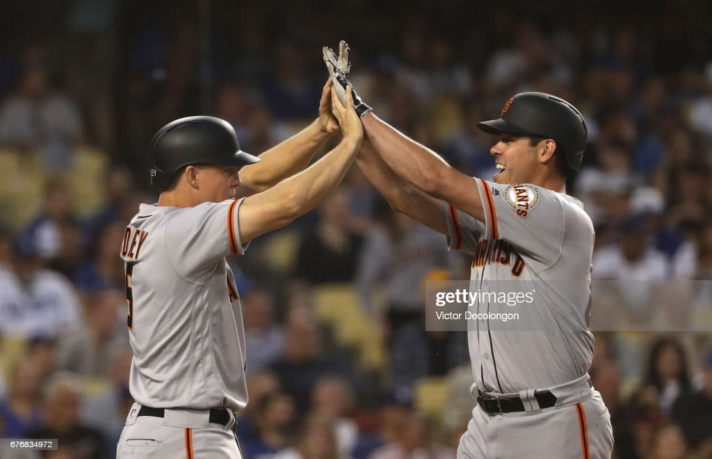 Nick Hundley #5 and Matt Moore #45 of the San Francisco Giants celebrate at homeplate after they scored on a double by teammate Brandon Belt #9 (not in photo) during the second inning of their MLB game against the Los Angeles Dodgers at Dodger Stadium on May 2, 2017 in Los Angeles, California.