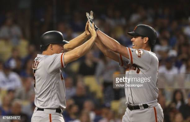 Nick Hundley and Matt Moore of the San Francisco Giants celebrate at homeplate after they scored on a double by teammate Brandon Belt during the...