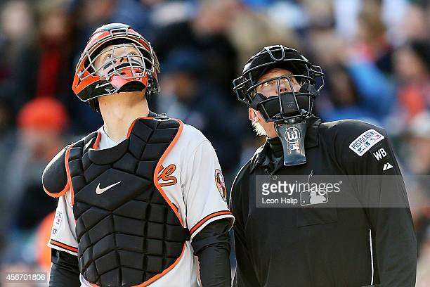Nick Hundley of the Baltimore Orioles and Home plate umpire Jeff Kellogg look up at a drone flying overhead during Game Three of the American League...