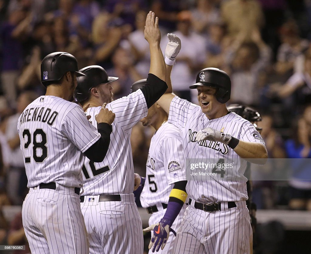 Nick Hundley #4 of the Colorado Rockies celebrates at home plate after his grand slam home run with teammates Nolan Arenado #28 of the Colorado Rockies, Mark Reynolds #12 of the Colorado Rockies and Carlos Gonzalez #5 of the Colorado Rockies against the Arizona Diamondbacks in the eighth inning at Coors Field on September 2, 2016 in Denver, Colorado.