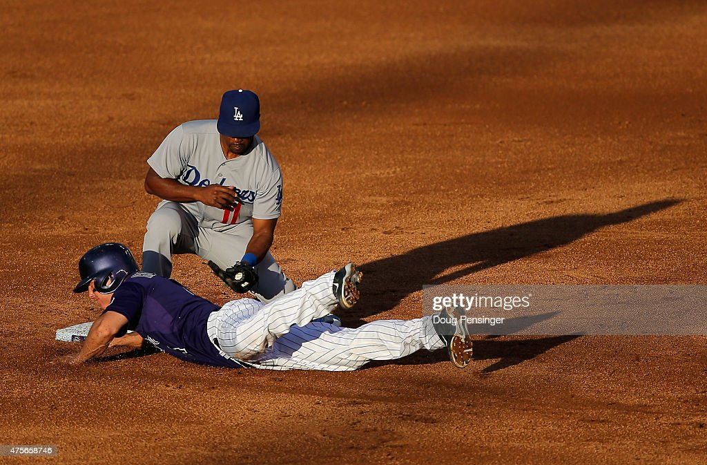 Nick Hundley #4 of the Colorado Rockies dives safely back to second base as shortstop Jimmy Rollins #11 of the Los Angeles Dodgers takes a late pick off throw in the third inning during game two of a double header at Coors Field on June 2, 2015 in Denver, Colorado.