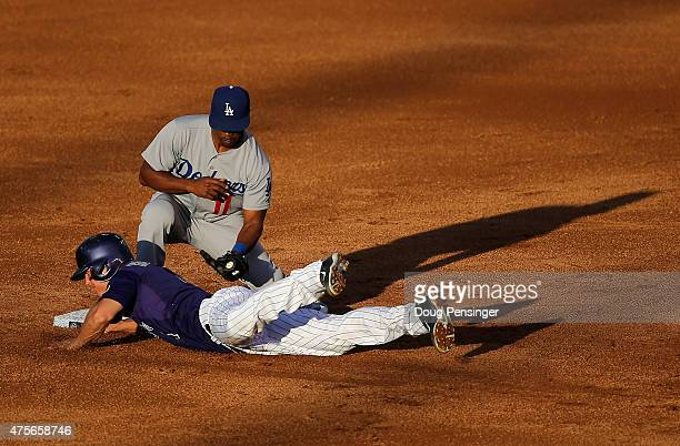 Nick Hundley of the Colorado Rockies dives safely back to second base as shortstop Jimmy Rollins of the Los Angeles Dodgers takes a late pick off...
