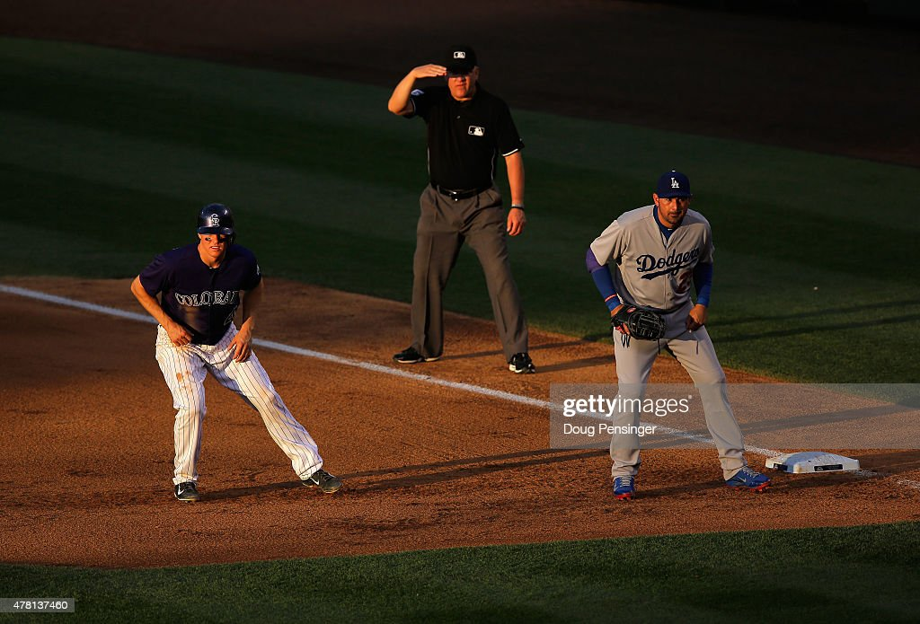Nick Hundley #4 of the Colorado Rockies leads off first base as first baseman Adrian Gonzalez #23 of the Los Angeles Dodgers plays defense and umpire Jeff Nelson oversees the action during game two of a double header at Coors Field on June 2, 2015 in Denver, Colorado.