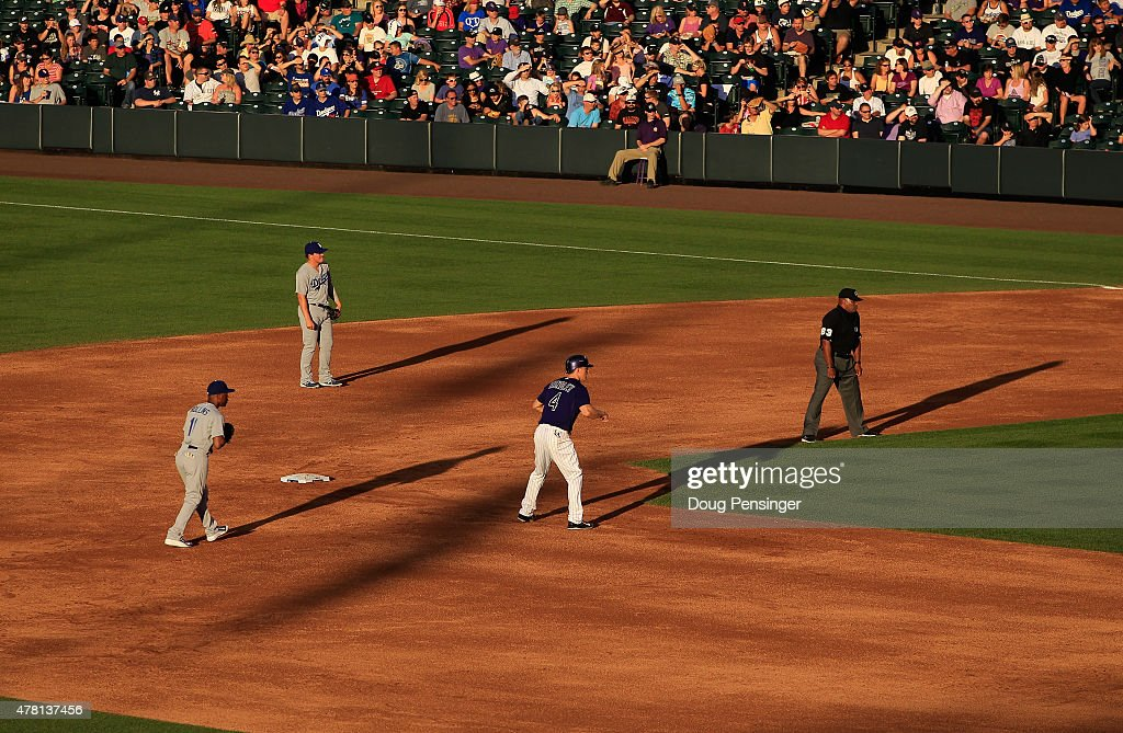 Nick Hundley #4 of the Colorado Rockies leads off second base as shortstop Jimmy Rollins #11 and second baseman Enrique Hernandez #14 of the Los Angeles Dodgers play defense and umpire Laz Diaz oversees the action during game two of a double header at Coors Field on June 2, 2015 in Denver, Colorado.