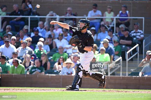 Nick Hundley of the Colorado Rockies throws the ball to second base between innings against the Los Angeles Angels of Anaheim at Salt River Fields at...