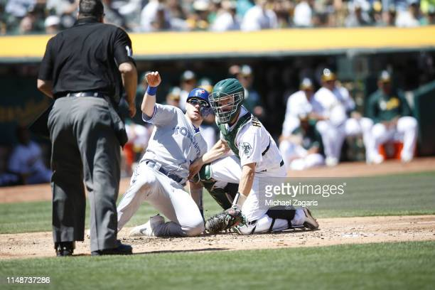 Nick Hundley of the Oakland Athletics tags Danny Jansen of the Toronto Blue Jays out at home during the game at the OaklandAlameda County Coliseum on...