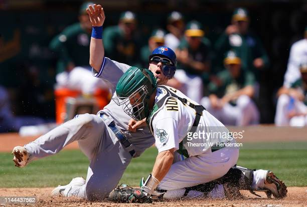 Nick Hundley of the Oakland Athletics tags out Danny Jansen of the Toronto Blue Jays at home plate in the top of the third inning of a Major League...
