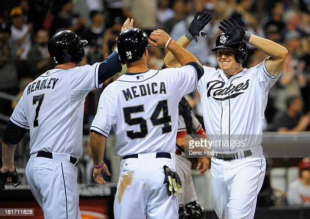 Nick Hundley of the San Diego Padres right is congratulated by Chase Headley and Tommy Medica after hitting a threerun homer during the sixth inning...