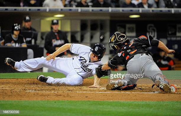 Nick Hundley of the San Diego Padres scores ahead of the tag of Rob Brantly of the Miami Marlins during the fourth inning of a baseball game at Petco...