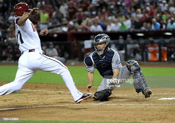 Nick Hundley of the San Diego Padres tags out Wil Nieves of the Arizona Diamondbacks at home plate at Chase Field on May 24 2013 in Phoenix Arizona
