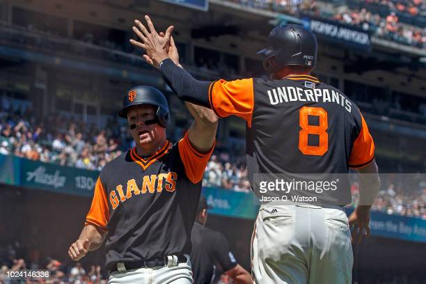 Nick Hundley of the San Francisco Giants and Hunter Pence celebrate after scoring runs on a triple hit by Steven Duggar during the fourth inning...
