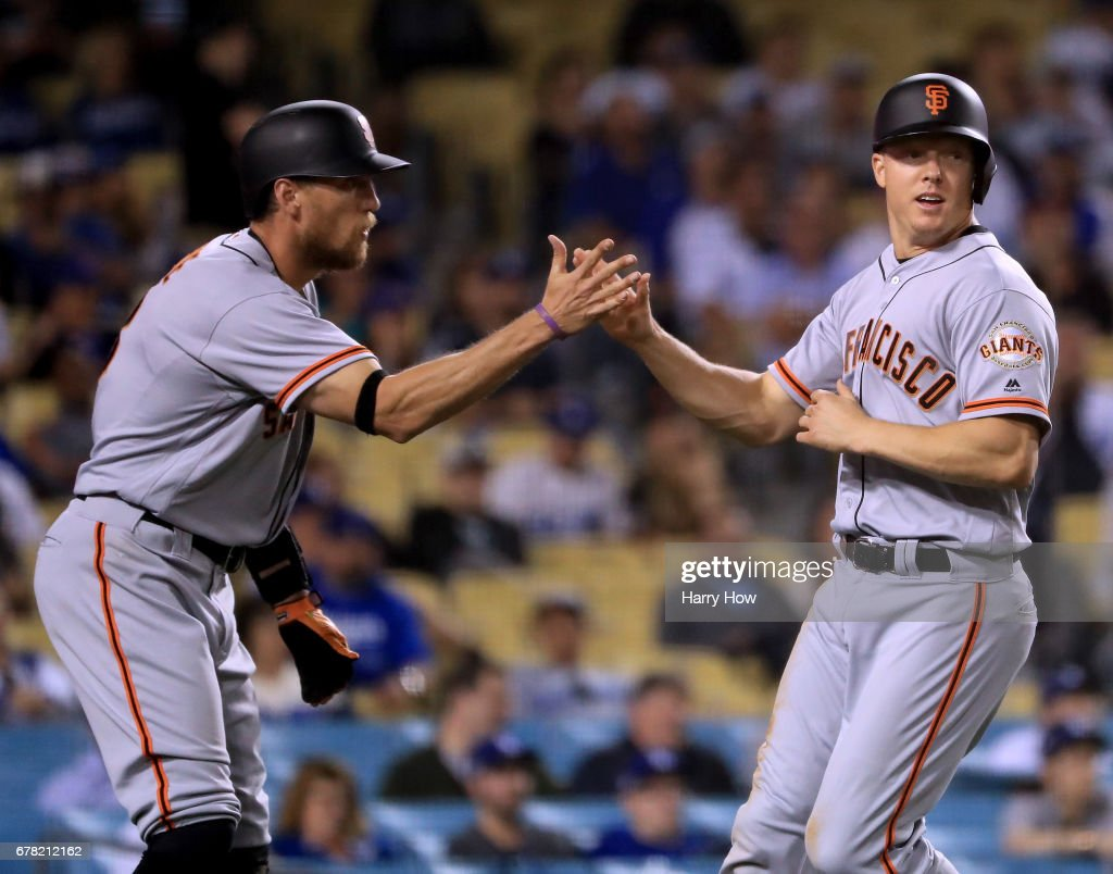 Nick Hundley #5 of the San Francisco Giants celebrates his run with Hunter Pence #8 to take a 3-1 lead over the Los Angeles Dodgers during the 11th inning at Dodger Stadium on May 3, 2017 in Los Angeles, California.