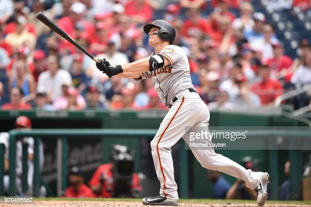 Nick Hundley of the San Francisco Giants hits a three run home run in the third inning during a baseball game against the Washington Nationals at...