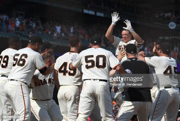 Nick Hundley of the San Francisco Giants jumps in the air at home plate celebrating with teammates after he hit a walk off solo home run against the...