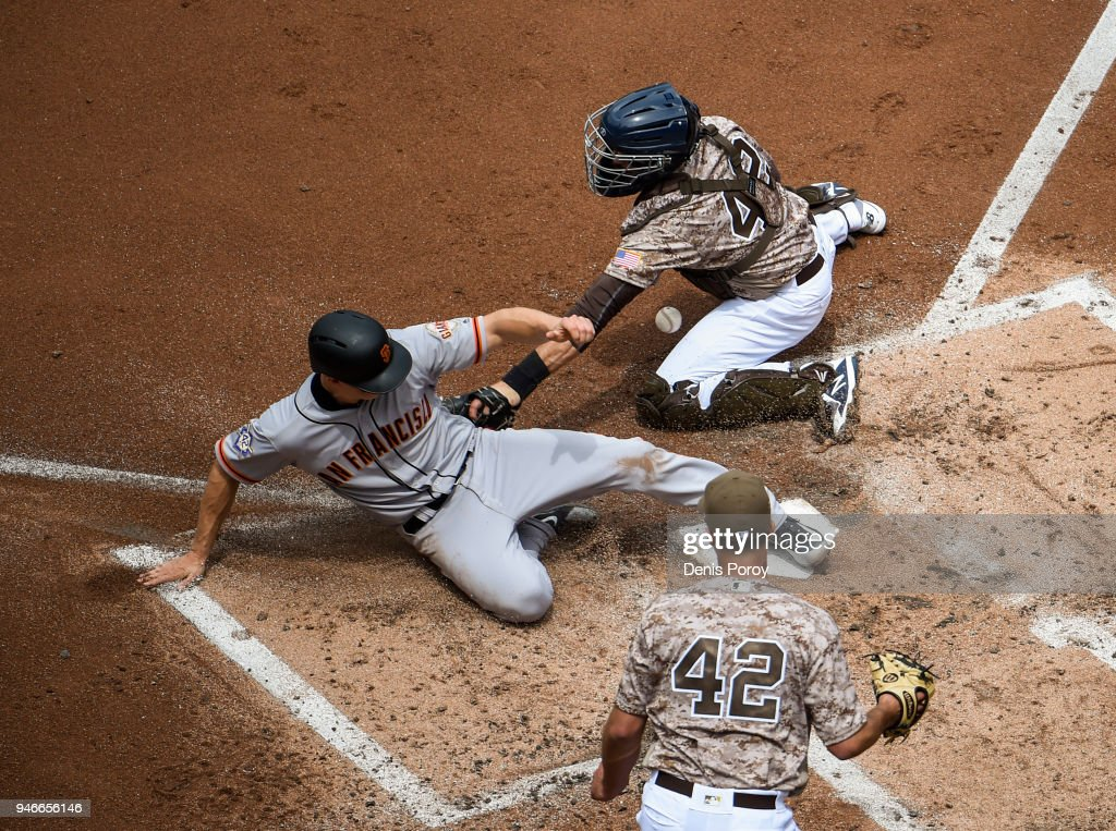 Nick Hundley #5 of the San Francisco Giants, (L) scores ahead of the tag of Austin Hedges #18 of the San Diego Padres, (R) as Joey Lucchesi looks on during the second inning of a baseball game at PETCO Park on April 15, 2018 in San Diego, California. All players are wearing #42 in honor of Jackie Robinson Day.