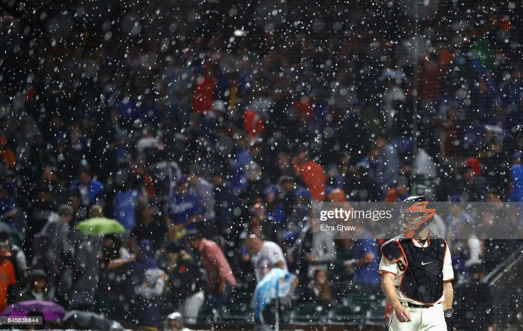 Nick Hundley #5 of the San Francisco Giants walks back to the dugout after their game against the Los Angeles Dodgers was delayed in the first inning because of rain at AT&T Park on September 11, 2017 in San Francisco, California.