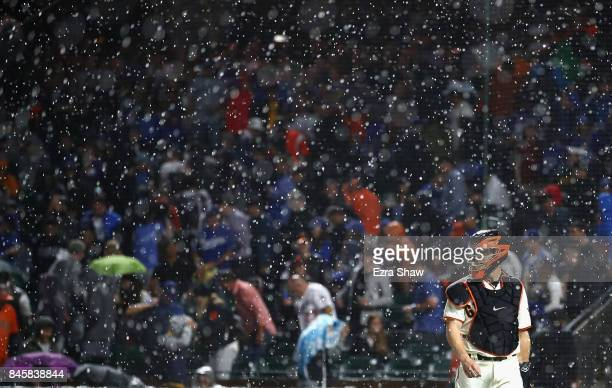 Nick Hundley of the San Francisco Giants walks back to the dugout after their game against the Los Angeles Dodgers was delayed in the first inning...