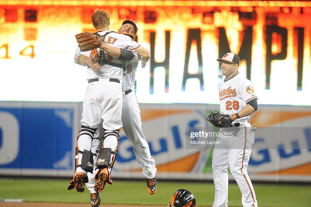 Nick Hundley #40 (L), Tommy Hunter #29 (C) and Steve Pearce #28 (R) of the Baltimore Orioles celebrate on the field after the Orioles clinch the American League East Division during a baseball game against the Toronto Blue Jays on September 16, 2014 at Oriole Park at Camden Yards in Baltimore, Maryland.