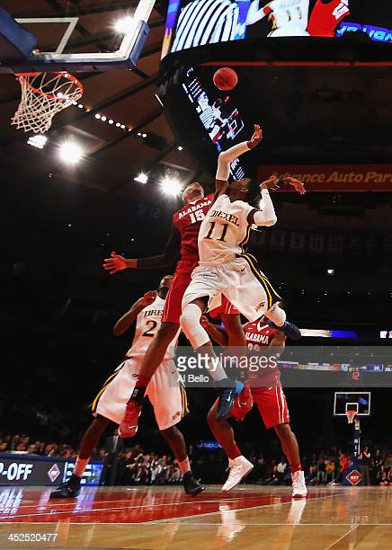 Nick Jacobs of the Alabama Crimson Tide and Tavon Allen of the Drexel Dragons battle for a rebound during their consolation game of the NIT Season...