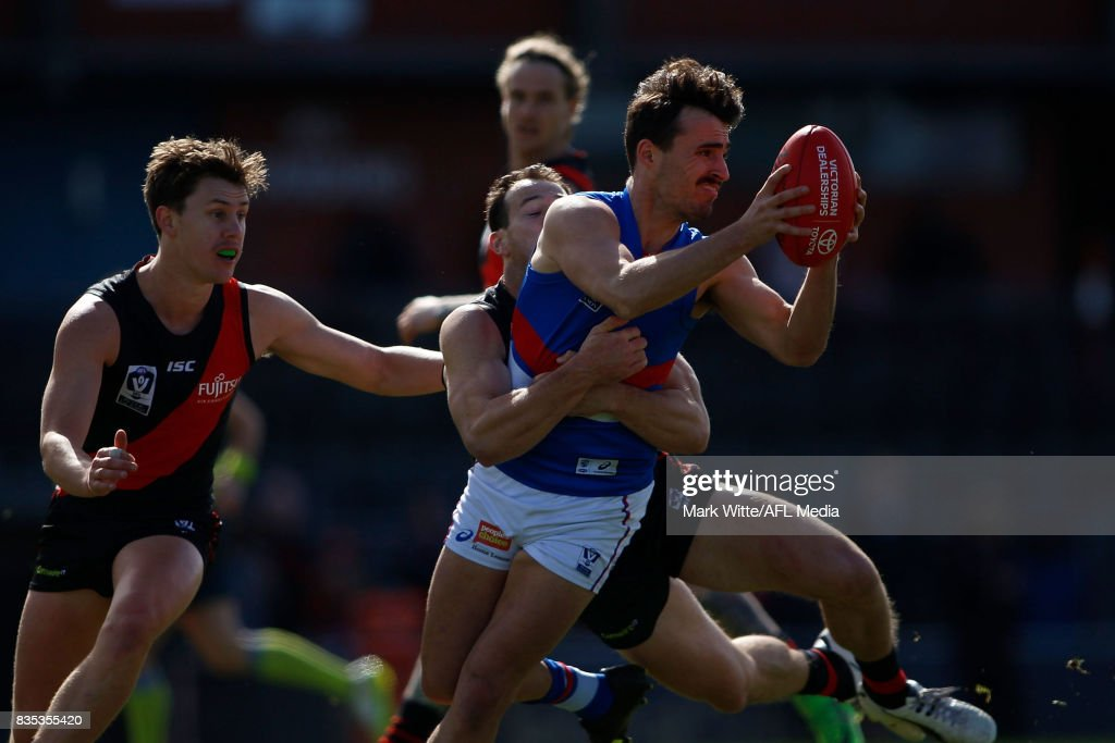 Nick Jamieson of Footscray Bulldogs gets tackled by Matt Deaof Essendon Bombers during the round 18 VFL match between the Essendon Bombers and Footscray Bulldogs at Windy Hill on August 19, 2017 in Melbourne, Australia.