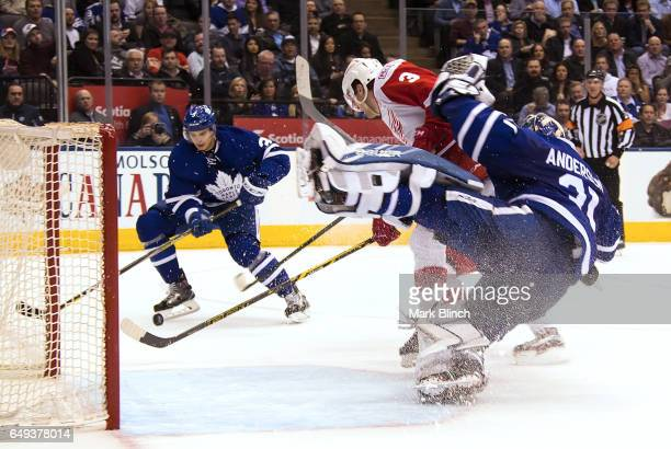 Nick Jensen of the Detroit Red Wings hits Frederik Andersen of the Toronto Maple Leafs as Alexey Marchenko of the Toronto Maple Leafs tries to clear...
