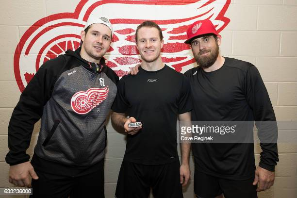 Nick Jensen of the Detroit Red Wings holds the puck from his first NHL goal with teammates Xavier Ouellet and Henrik Zetterberg after an NHL game...