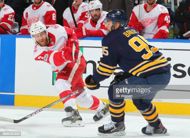 Nick Jensen of the Detroit Red Wings shoots the puck while Justin Bailey of the Buffalo Sabres defends during an NHL game on October 24, 2017 at...