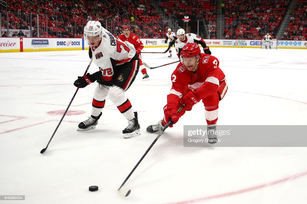Nick Jensen #3 of the Detroit Red Wings tries to beat Thomas Chabot #72 of the Ottawa Senators to the puck in the first period at Little Caesars Arena on March 31, 2018 in Detroit, Michigan.