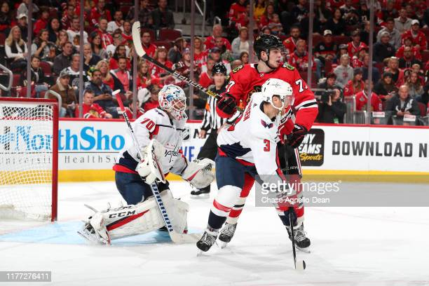 Nick Jensen of the Washington Capitals and Kirby Dach of the Chicago Blackhawks get physical in front of goalie Braden Holtby at the United Center on...