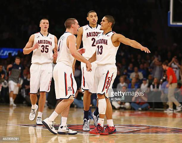 Nick Johnson of the Arizona Wildcats celebrates a basket with TJ McConnell their Semi Final game of the NIT Season Tip Off against the Drexel Dragons...