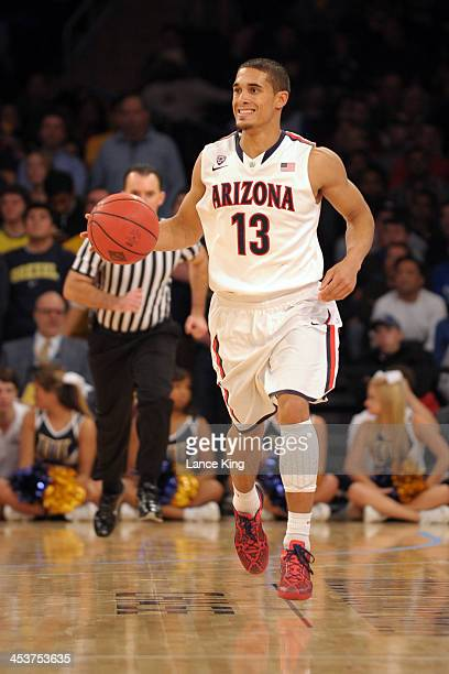 Nick Johnson of the Arizona Wildcats dribbles up court against the Drexel Dragons during their semifinal game of the NIT Season TipOff at Madison...