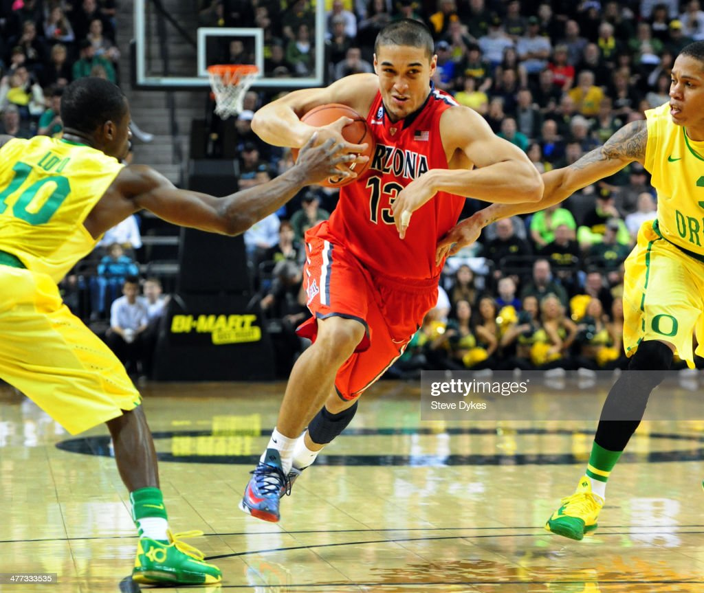 Nick Johnson #13 of the Arizona Wildcats drives to the basket on Johnathan Loyd #10 and Joseph Young #3 of the Oregon Ducks during the second half of the game at Matthew Knight Arena on March 8, 2014 in Eugene, Oregon. Oregon won the game 64-57.