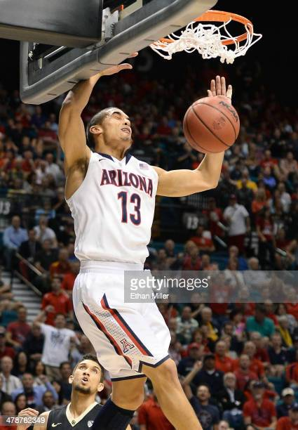Nick Johnson of the Arizona Wildcats dunks off an alleyoop pass against Askia Booker of the Colorado Buffaloes during a semifinal game of the Pac12...