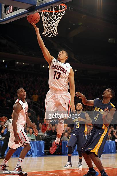 Nick Johnson of the Arizona Wildcats goes to the hoop against Frantz Massenat of the Drexel Dragons during their semifinal game of the NIT Season...
