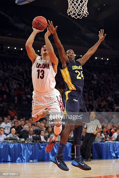 Nick Johnson of the Arizona Wildcats goes to the hoop against Rodney Williams of the Drexel Dragons during their semifinal game of the NIT Season...