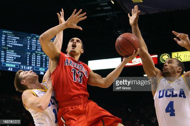 Nick Johnson of the Arizona Wildcats goes up for a shot between David Wear and Norman Powell of the UCLA Bruins in the second half during the...