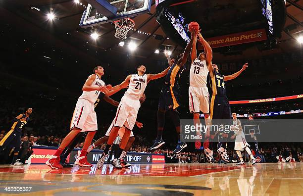 Nick Johnson of the Arizona Wildcats grabs a rebound against Dartaye Ruffin of the Drexel Dragons and Damion Lee of the Drexel Dragons during their...