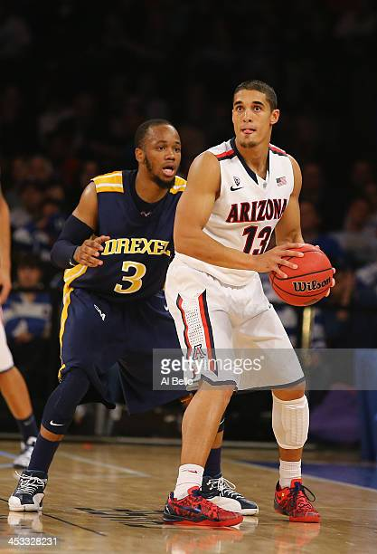 Nick Johnson of the Arizona Wildcats in action against Chris Fouch of the Drexel Dragons during their Semi Final game of the NIT Season Tip Off at...