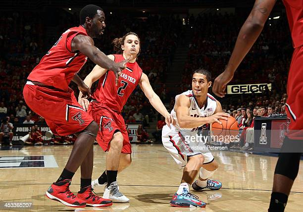 Nick Johnson of the Arizona Wildcats looks to pass around Dusty Hannahs of the Texas Tech Red Raiders during the first half of the college basketball...